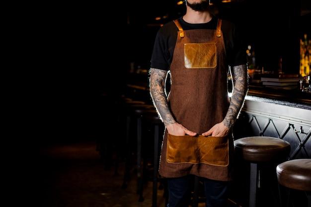 Barman z tatuażem ubrany w brązowy fartuch