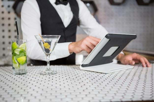 Barman za pomocą cyfrowego tabletu w barze licznika