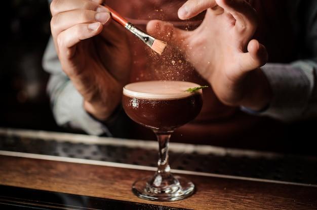 Barman zdobi koktajl złotym proszkiem. magiczny obraz