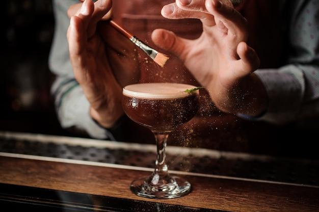 Barman zdobi koktajl złotym proszkiem