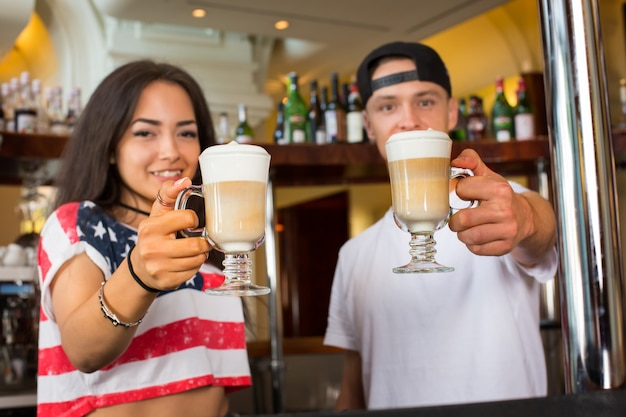 Barmani oferujący kawowe cappuccino