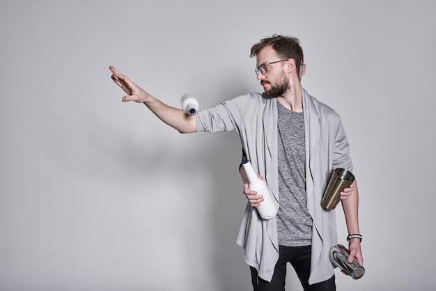 Barmani żonglują butelkami i trzęsą się na białej ścianie, bliźniacy