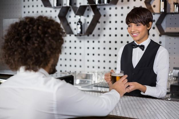 Barmanka podaje człowiekowi napój