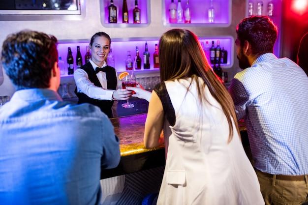 Barmanka podaje napój kobiecie