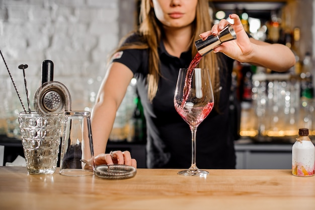 Barmanka przygotowuje koktajle w barze dla swoich klientów