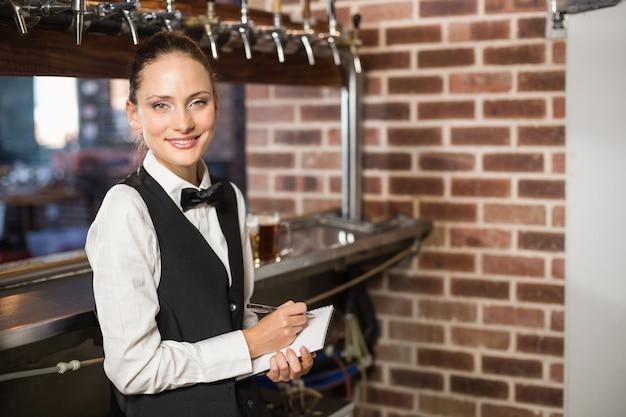 Barmanka przyjmuje zamówienia na notatnik