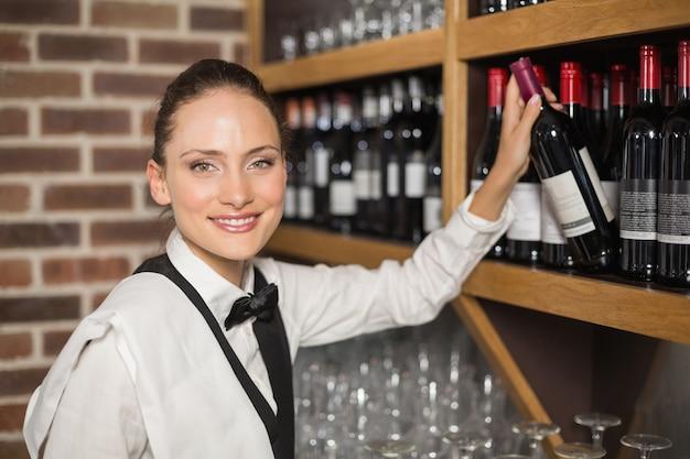 Barmanka wyjmuje butelkę z półki