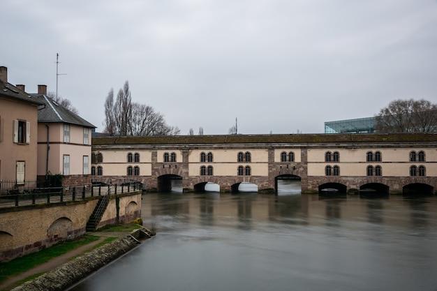 Barrage vauban otoczony wodą i budynkami pod zachmurzonym niebem w strasburgu we francji