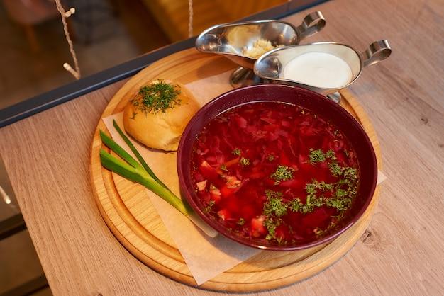 Barszcz ukraiński na drewnianej tacy na stole w restauracji