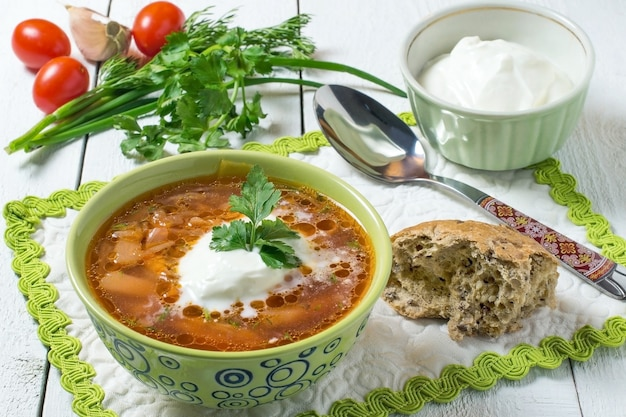 Barszcz ze śmietaną w zielonej misce pomidory czosnek świeże zioła na białym drewnianym tle
