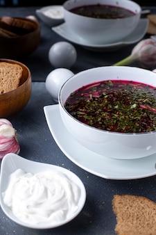 Barszczowa czerwona zupa jarzynowa z chlebem i śmietaną na szarym biurku