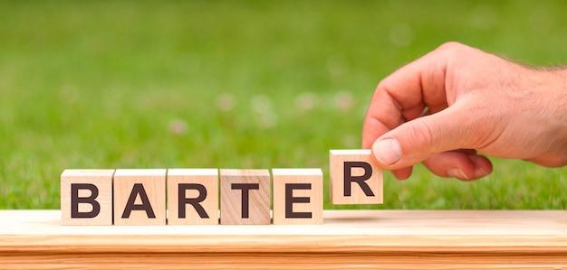 Barter to słowo zapisane na drewnianych klockach. ręka mężczyzny trzyma drewnianą kostkę z literą r od słowa barter