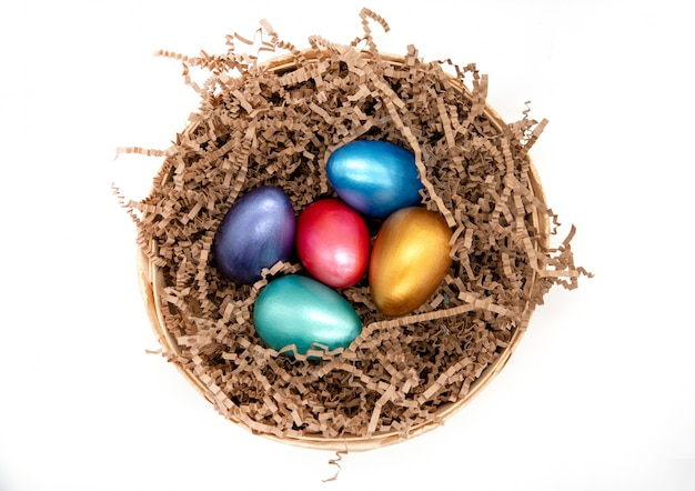 Barwi easter jajka w koszu odizolowywającym na bielu