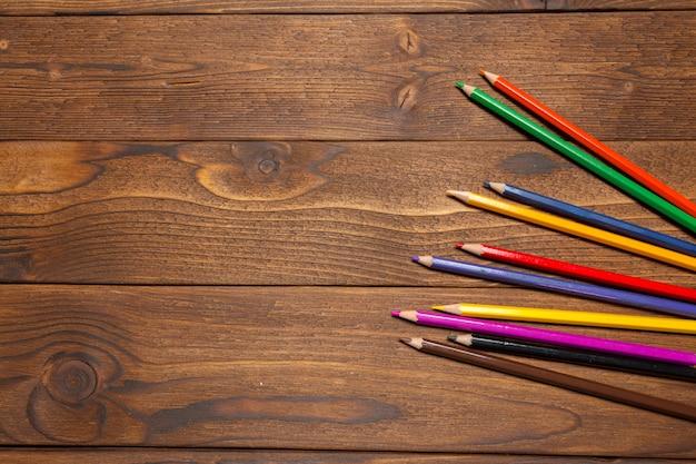 Barwi ołówki na drewnianej desce, odgórny widok