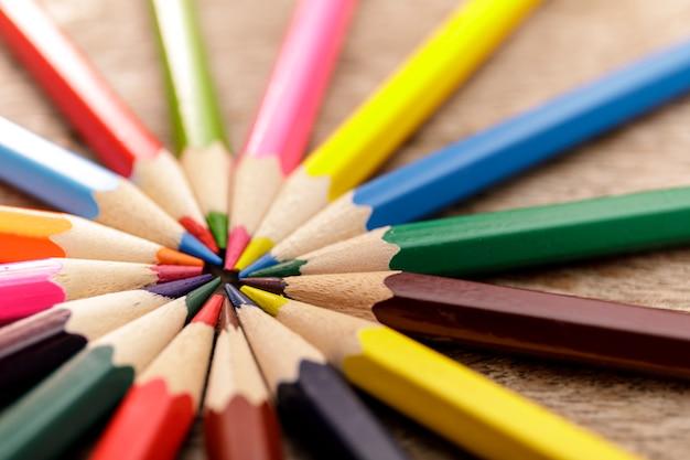 Barwi ołówki w okręgu na starym nieociosanym drewnianym tle