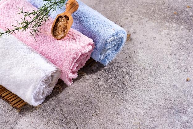 Barwi ręczniki z zielonymi liśćmi i łyżką sól na bambus macie i kamienia stole, copyspace