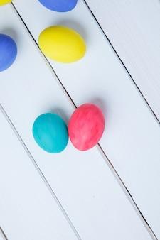 Barwi wielkanocnych jajka na białym stole. wesołych świąt wielkanocnych