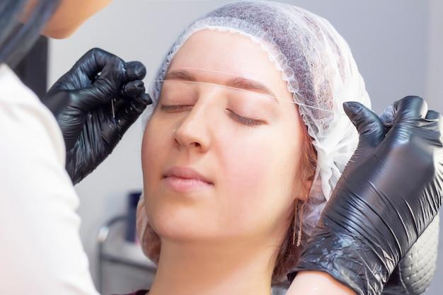 Barwienie brwi. salon piękności. dziewczyna leży z zamkniętymi oczami na procedurze farbowania brwi.