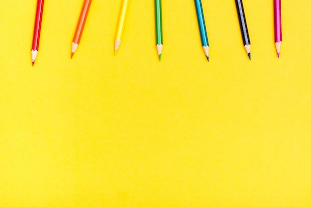 Barwioni drewniani ołówki na żółtym tle