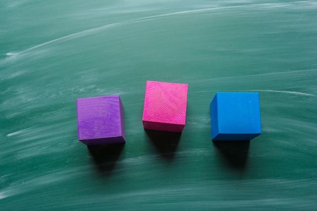 Barwioni drewniani sześciany na zielonym chalkboard