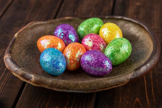 Barwioni easter jajka na glinianym talerzu. koncepcja wakacje w kolorach czerwonym, żółtym, zielonym, niebieskim.