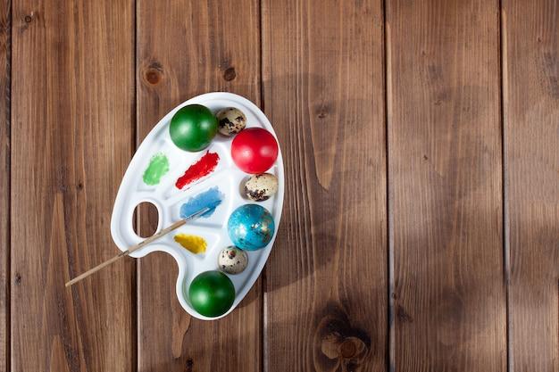 Barwioni jajka i farba na drewnianym stole, wielkanocny tło