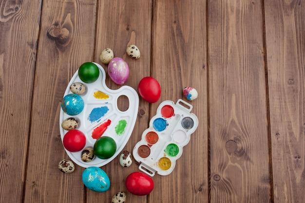 Barwioni jajka i farba na drewnianym stole