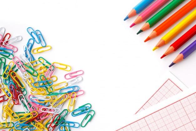 Barwioni ołówki i papper klamerka odizolowywają na bielu