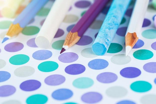 Barwioni ołówki i szkolna kreda na pastelowym tle punkt z przestrzenią dla teksta.