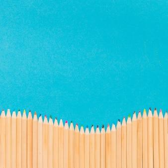 Barwioni ołówki na błękitnym tle