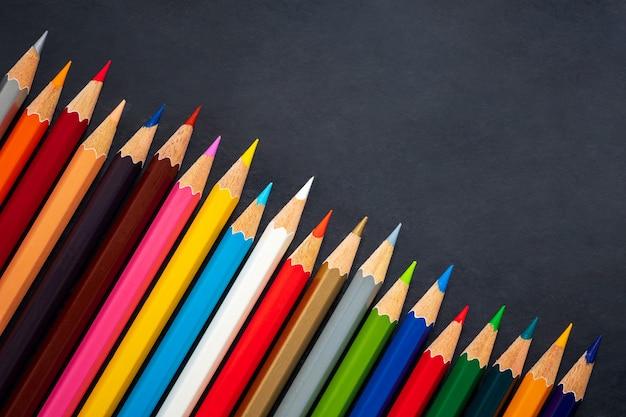 Barwioni ołówki na chalkboard tle
