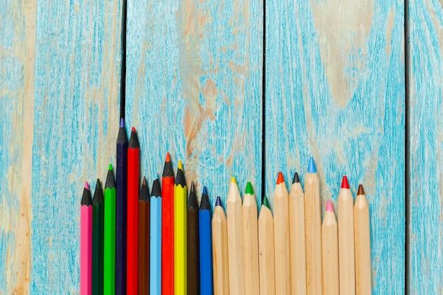 Barwioni ołówki na drewnianym deski tle