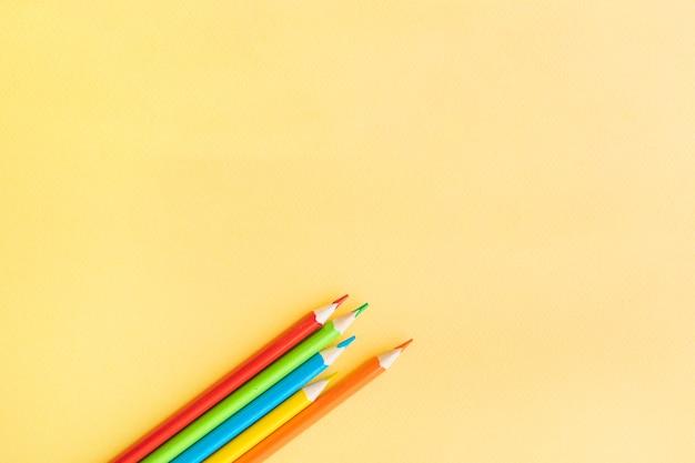 Barwioni ołówki na żółtym tle