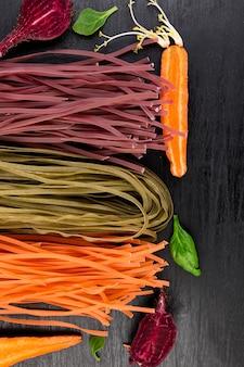 Barwiony surowy warzywo wegetariański makaron z burakami, marchewką i szpinakiem. leżał płasko. skopiuj miejsce widok z góry. rama.