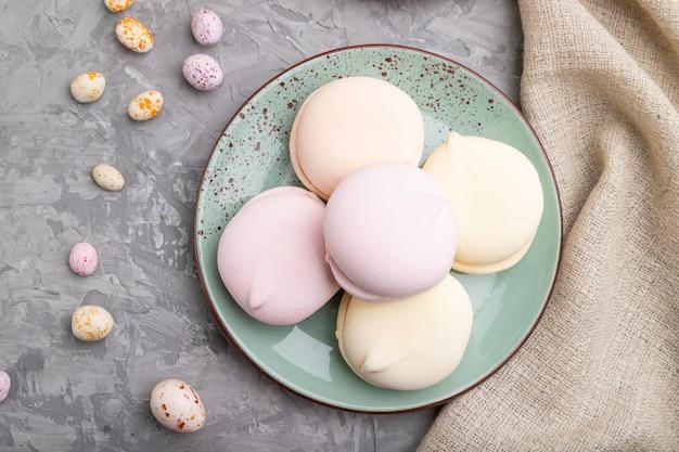 Barwiony zefir lub marshmallow z filiżanką kawy i drażetkami na szarym betonowym tle. widok z góry, z bliska.