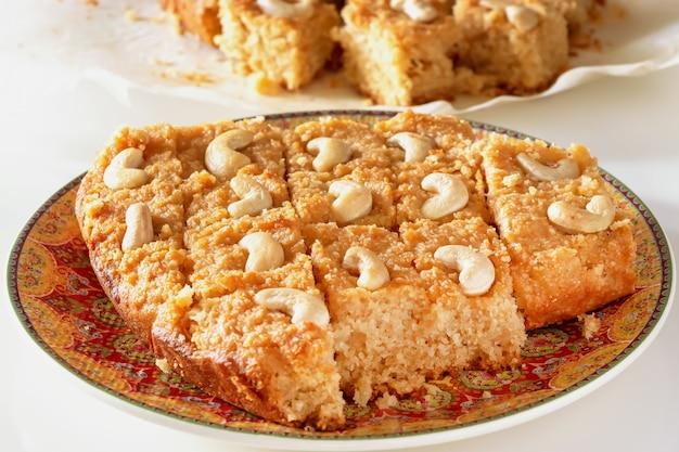 Basbousa lub namoora tradycyjny arabski tort manna z orzechami nerkowca i syropem. selektywne skupienie.