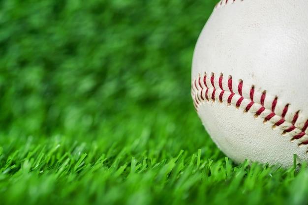 Baseball używać stawiający na zielonej trawy tle.