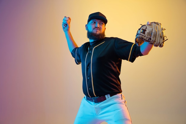 Baseballista, miotacz w czarnym mundurze, ćwiczy i trenuje na gradientowym tle w świetle neonu.