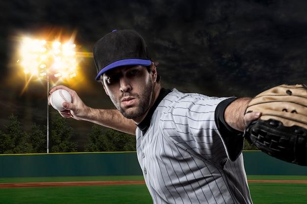 Baseballista na niebieskim mundurze na stadionie baseballowym.