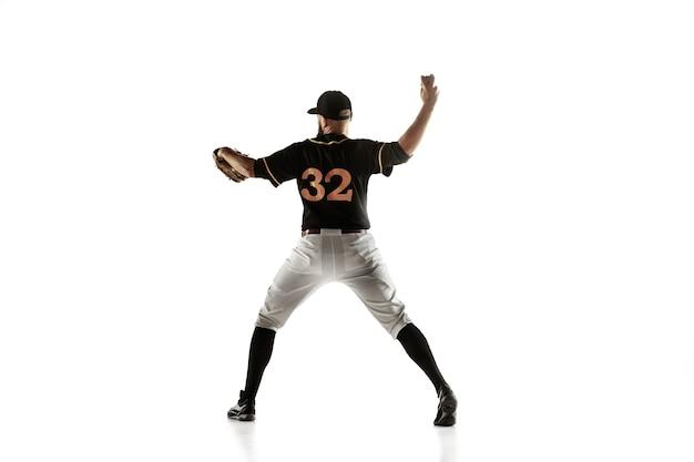 Baseballista w czarnym mundurze ćwiczy i trenuje na białym tle
