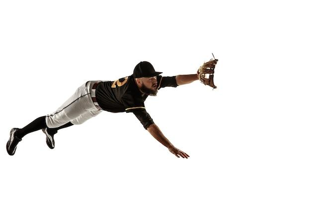 Baseballista w czarnym mundurze ćwiczy na białym tle.