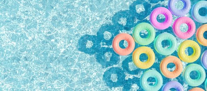 Basen widziany z góry z wieloma pierścieniami pływającymi w pastelowych kolorach