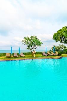 Basen z krzesłami i parasol wokół basenu z oceanem