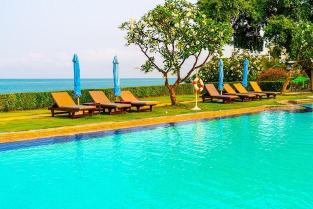 Basen z krzesłami lub basen z łóżkiem i parasol wokół basenu z tłem morskim - koncepcja wakacji i wakacji