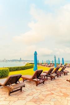Basen z krzesłami lub basen z łóżkiem i parasol wokół basenu z widokiem na plażę morską w pattaya w tajlandii