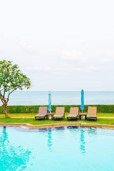 Basen z krzesłami lub basen z łóżkiem i parasolem wokół basenu