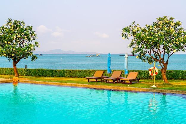 Basen z krzesłami wokół basenu z morzem