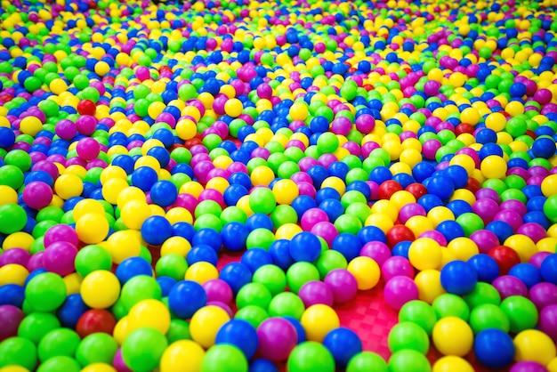 Basen z plastikowymi kulkami w kolorze zielonym, niebieskim, różowym, czerwonym i żółtym.