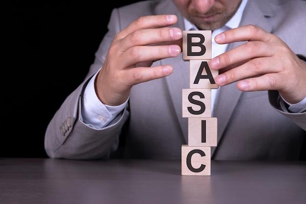 Basic, słowo zapisane na drewnianych kostkach, klocki na tle mężczyzny, biznesmena w szarym garniturze.