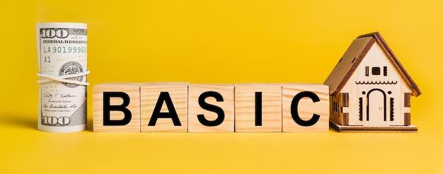 Basic z miniaturowym modelem domu i pieniędzmi na żółtym tle. pojęcie biznesu, finansów, kredytu, podatków, nieruchomości, domu, mieszkania